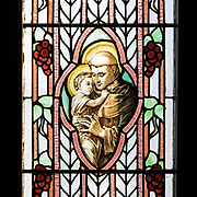 St. Anthony was the patron saint of Louise Drexel Morrell's uncle, Anthony Drexel.<br /> <br /> St. Anthony of Padua (1195-1231) was a Franciscan priest admired for his knowledge of scripture and his eloquent sermons. Because of his education, St. Francis of Assisi put him in charge of the education of Franciscan friars, and early images usually depict him holding a book. In the 16th century, a story became popular about St. Anthony having a vision of the Christ child, and he was often shown holding a book with a miniature child standing on it. The imagery continued to change and eventually the child was shown at normal size, and replaced the book. St. Anthony is now usually shown as a Franciscan monk holding a child. This window is closely based on a popular image used on early 20th-century prayer cards. The glass artist even kept the peculiar positions of Anthony's hands - try making your own fingers do that.