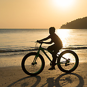 Silhouette of a boy on a bike on Cenang beach, Langkawi, Malaysia at sunset