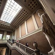 A grand stairway inside the main entrance to the British Museum in London. At right of frame is The Townley Caryatid, a Roman sculpture dated to about AD 140-170, on display near the main entrance of the British Museum in London. It was found around 1585-90 near the Via Applie outside Rome. It was aacquired by the Peretti family and was kept at the Villa Peretti Montalto, later Negroni. In 1784 the contents of the Villa were sold, and the Caryatid was afterwards bought by Charles Townley. The British Museum in downtown London us dedicated to human history and culture and has about 8 million works in its permanent collection.