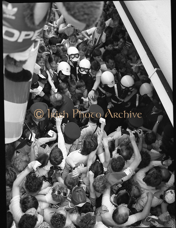 Irish Soccer Team Welcomed Home.   (R81)..1988..19.06.1988..06.19.1988..19th June 1988..After their great success in Germany in Euro 88, the Irish soccer team had a triumphant homecoming. An Taoiseach, Charles Haughey TD and his government were to the forefront of the welcome. Thousands of fans thronged the airport and all the approach roads in the hope of seeing the team. The full squad is as follows..1.GK.Packie Bonner. Celtic.2.DF.Chris Morris. Celtic.3.DF.Chris Hughton  Tottenham Hotspur.4.DF.Mick McCarthy. Celtic.5.DF.Kevin Moran. Manchester United.6.MF.Ronnie Whelan. Liverpool.7.MF.Paul McGrath. Manchester United.8.MF.Ray Houghton. Liverpool.9.FW.John Aldridge. Liverpool.10.FW.Frank Stapleton Derby County.11.MF.Tony Galvin. Sheffield Wednesday.12.FW.Tony Cascarino. Millwall.13.MF.Liam O'Brien. Manchester United.14.FW.David Kelly. Walsall.15.MF.Kevin Sheedy. Everton.16.GK.Gerry Peyton. Bournemouth.17.FW.John Byrne. Le Havre.18.FW.John Sheridan. Leeds United.19.DF.John Anderson. Newcastle United.20.FW.Niall Quinn. Arsenal..Image shows the  Gardaí trying to clear a path for the Irish Team as the try to board the open top bus for their tour through Dublin City for the civic reception.