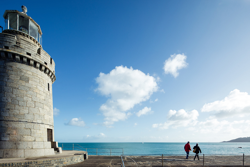 A couple walking along the walkway leading away from Castle Cornet Lighthouse, with views out to the calm blue sea, on a sunny day in Guernsey, Channel Islands
