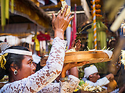 19 JULY 2016 - TAMPAKSIRING, GIANYAR, BALI, INDONESIA: A woman participates in a blessing on the first day of a ceremony to honor the anniversary Pura Agung temple, one of the most important Hindu temples on Bali. This year's ceremony is the most important in years because it falls on the 50 year cycle of the temple's founding. This year's ceremony lasts for 11 days.      PHOTO BY JACK KURTZ
