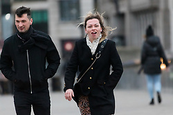 © Licensed to London News Pictures. 09/02/2020. London, UK. A couple walk across London Bridge during windy weather this morning. Rain and windy weather is forecast today as Storm Ciara reaches the capital. Photo credit: Vickie Flores/LNP