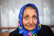 Portrait of Elena - a Roma woman waiting at a bus stop in Marginenii de Jos for getting back home from work.