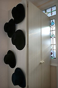 5 hats belonging to 5 different men in an Orthodox Jewish family, hanging in the hallway of an home in Stamford Hill, London.