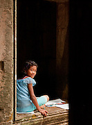 A young girl sits drawing in the doorway of an old temple near Angkor Wat at Angkor, Siem Reap Province, Cambodia