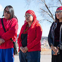 Jody Lynch, 47, left, Roqui Jones, 45, center, and Amberina Tolino, 30, right, listen to the song sung by Dan Nanamkin during the Missing and Murdered Indigenous Women and Girls Walk, in Ft. Defiance Friday.