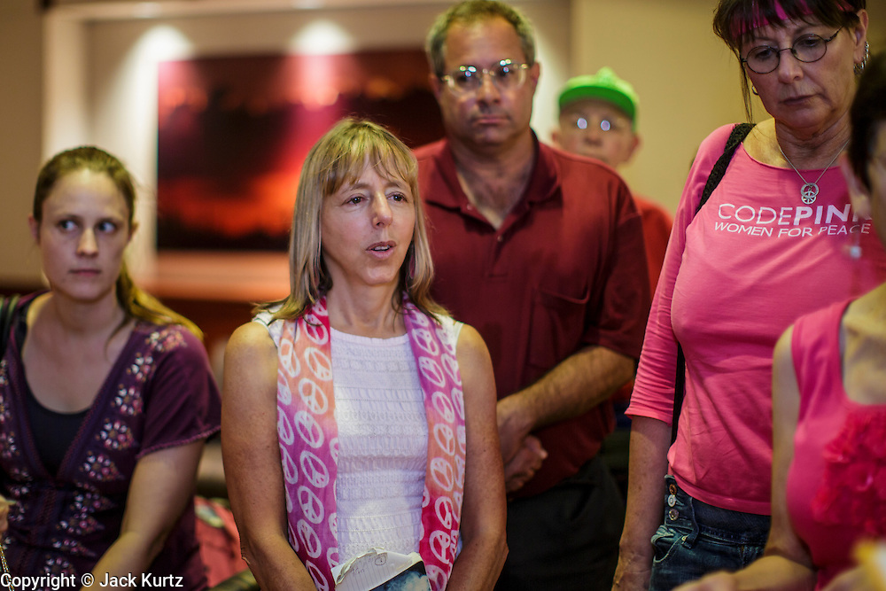 """31 JULY 2012 - PHOENIX, AZ:  MEDEA BENJAMIN, center, and other members of Code Pink, wait in the lobby of the governor's office at the Arizona State Capitol Tuesday. Medea is a political activist, best known for co-founding Code Pink and, along with her husband, activist and author Kevin Danaher, the fair trade advocacy group Global Exchange. She was also a Green Party candidate in 2000 for the United States Senate. She appeared in Phoenix to promote her new book, """"Drone Warfare: Killing by Remote Control."""" She, and other members of Code Pink, presented a letter to Arizona Gov. Jan Brewer protesting Brewer's request to use the state's airspace to train drone pilots.  PHOTO BY JACK KURTZ"""