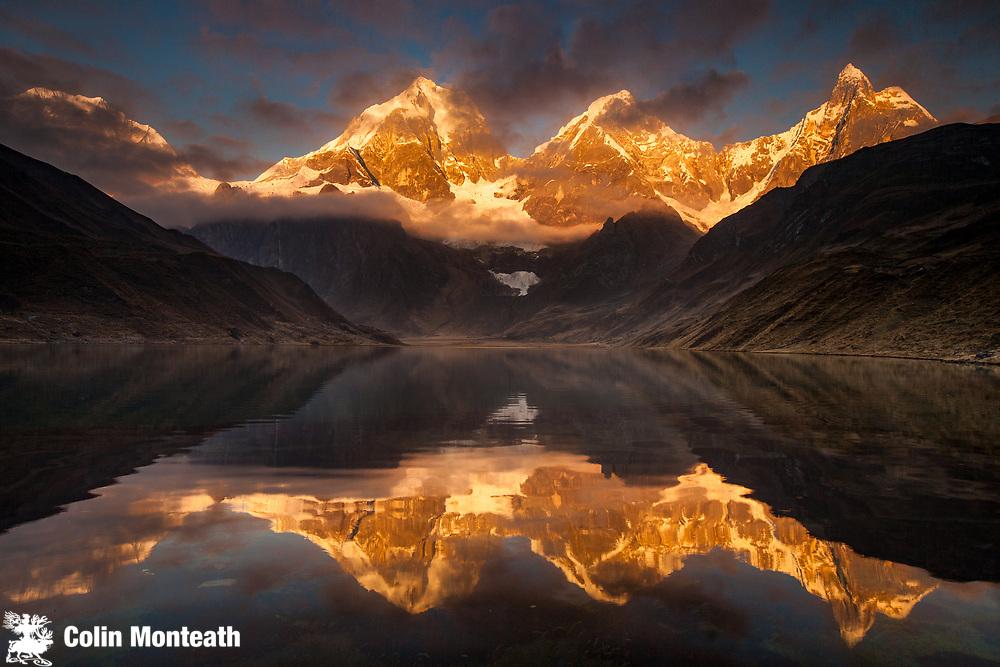 Carhuacocha lake, sunrise reflection on Siula Grande, Yerupaja and Jirishanca peaks, Andes mountains, Cordillera Huayhuash, northern Peru