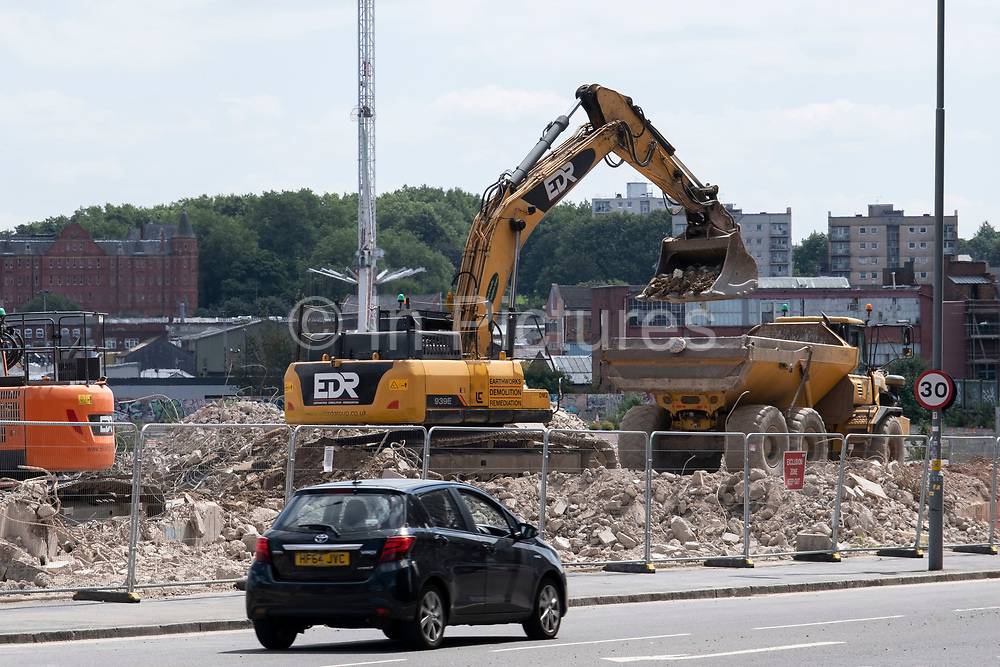 Digger working on tearing down and moving debris and rubble from an old multi storey car park as part of a development / redevelopment of old builindgs in the city centre on 14th July 2021 in Birmingham, United Kingdom. The city is under a long term and major redevelopment, with much of its industrial past being demolished and made into new flats for residential homes, as part of the Big City Plan.