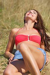 Smiling Woman Sunbathing amongst Beach Grass