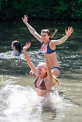 © Licensed to London News Pictures. 07/05/2018. London, UK. Lucy Abraham and Poppy Sheppard swim in Hampstead Heath Mixed Bathing Pond in north London as temperatures hit 28C on the hottest May bank holiday since 1999 on Monday, May 7, 2018. Photo credit: Tolga Akmen/LNP
