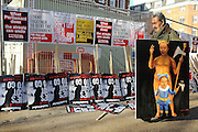© Licensed to London News Pictures. 30/11/2011, London, UK. KAYA MAR carries his satirical painting of David Cameron and Nick Clegg past stored placards before the march begins. Up to two million public sector workers are staging a strike over pensions in what is set to be the biggest walkout for a generation. Photo credit : Stephen Simpson/LNP
