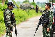 08 JULY 2013 - MAYO, PATTANI, THAILAND:  Thai soldiers stand watch as explosives teams and forensics experts work on a truck destroyed in an insurgent IED blast Monday. Eight Thai soldiers were injured - one seriouly and seven with minor injuries - when their truck was hit by an IED outside Mayo, Pattani province in southern Thailand Monday. The soldiers were returning from a teacher protection mission when their truck ran over the explosive. The attack was thought to be conducted by Muslim insurgents who have been battling the Thai government for greater autonomy. The conflict in southern Thailand has claimed about 5,000 lives since 2004.   PHOTO BY JACK KURTZ