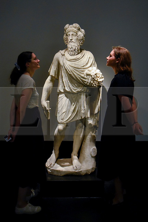 "© Licensed to London News Pictures. 25/06/2019. LONDON, UK. Staff members view ""Silvanus"" a 1st century AD Roman marble scuplture, from Galerie Chenel at a preview of Masterpiece London 2019, the world's leading cross-collecting art fair held in the grounds of the Royal Hospital Chelsea.  The fair brings together 157 international exhibitors presenting works from antiquity to the present day and runs 27 June to 3 July 2019.  Photo credit: Stephen Chung/LNP"