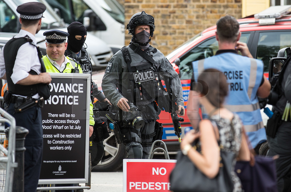 © Licensed to London News Pictures. 30/06/2015. London, UK. Armed officers leave the 'Exercise Strong Tower' area. The simulated terrorist attack is a joint exercise between the three emergency services which continued today in the Wood Wharf area, near Canary Wharf.  Photo credit : James Gourley/LNP