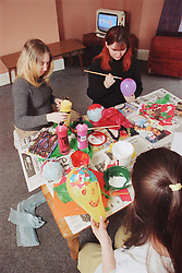 Group of residents painting balloons during arts and crafts lesson in women only homeless hostel,