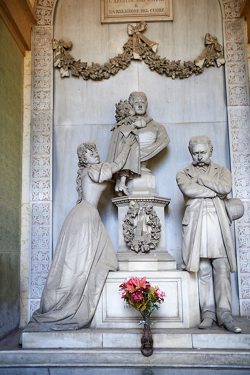 """Picture and image of the late borgeoise realistic style stone sculpture of the Gallino tomb sculpted by  G. Moreno 1894.  In the tomb, the bust that portrays the deceased Carolina receives the kiss of a child, probably the niece, supported by a young woman - the mother, or perhaps the elder sister - whose face is marked by pain; on the right an older man, presumably her husband, stands aside, almost absent, looking down at the ground. The most intimate tones and psychological introspection are grafted here in the language of bourgeois Realism: with undoubted technical virtuosity Moreno offers a rigorous """"quantitative"""" description of reality, dwelling on every single detail of faces, clothing, accessories and hairstyles . Section A, no 54, The monumental tombs of the Staglieno Monumental Cemetery, Genoa, Italy .<br /> <br /> Visit our ITALY PHOTO COLLECTION for more   photos of Italy to download or buy as prints https://funkystock.photoshelter.com/gallery-collection/2b-Pictures-Images-of-Italy-Photos-of-Italian-Historic-Landmark-Sites/C0000qxA2zGFjd_k<br /> If you prefer to buy from our ALAMY PHOTO LIBRARY  Collection visit : https://www.alamy.com/portfolio/paul-williams-funkystock/camposanto-di-staglieno-cemetery-genoa.html"""
