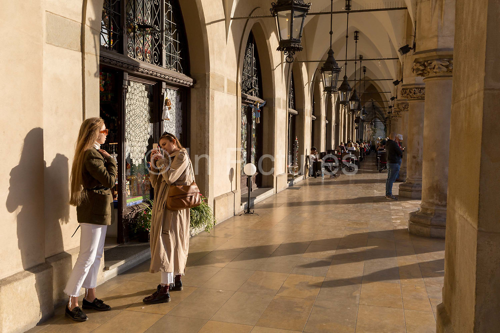 Young women take pictures of themselves in afternoon sunshine in the arched passageway of the Renaissance Cloth Hall on Rynek Glowny market square, on 22nd September 2019, in Krakow, Malopolska, Poland.