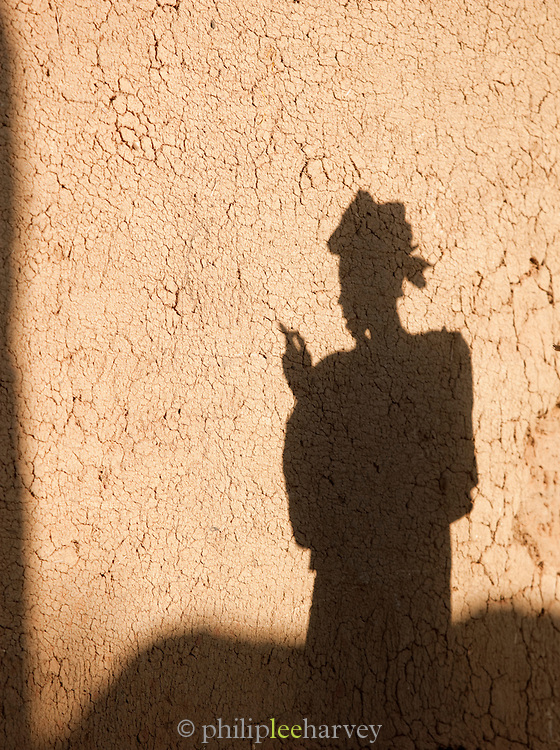 Shadow of a woman against a mud built house in Djenné, Mali