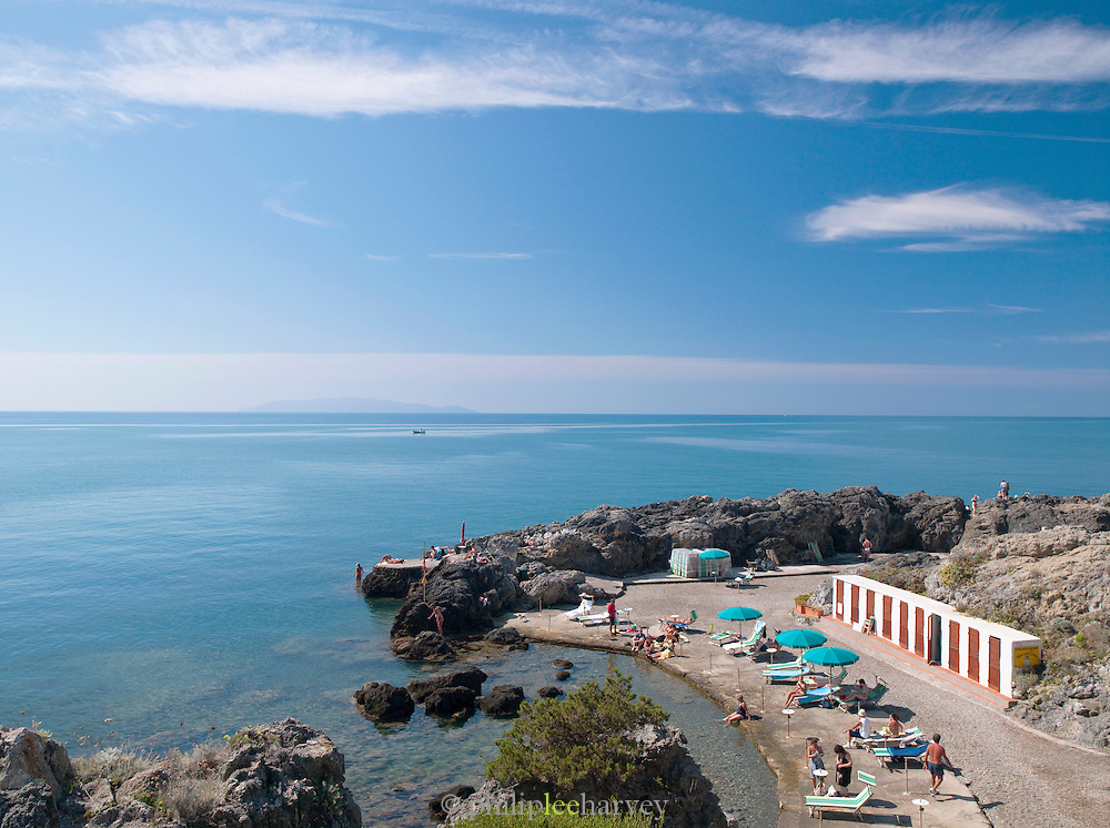 Tourists and local people relax in the water of the Mediterranean Sea at Talamone, a small Tuscan town in Italy