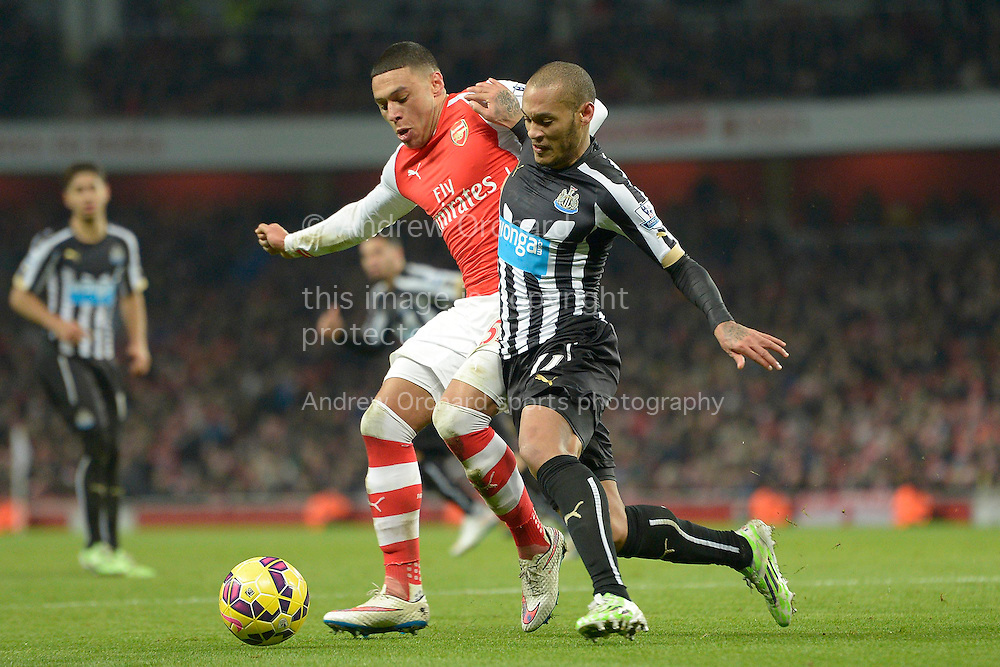 Yoan Gouffran of Newcastle United competing with Alex Oxlade-Chamberlain of Arsenal. Barclays Premier league match, Arsenal v Newcastle Utd at the Emirates Stadium in London on Saturday 13th December 2014.<br /> pic by John Patrick Fletcher, Andrew Orchard sports photography.