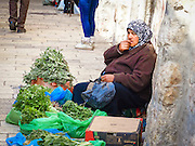 Israel, old city of Jerusalem, woman sells vegetables and herbs in the market street
