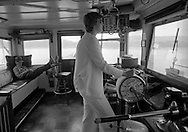 Lexie Palmore pilots the Delta Queen steamboat down the Ohio River, June, 1977.  She was the first female to become a riverboat pilot trainee, completing courses at the National River Academy in Helena, Arkansas.  She began her interest in riverboating as a passenger on the Delta Queen, later becoming a cabin maid.  She now pursues her life-long interest in painting from her home in Leadville, Colorado...Harry Louden in background