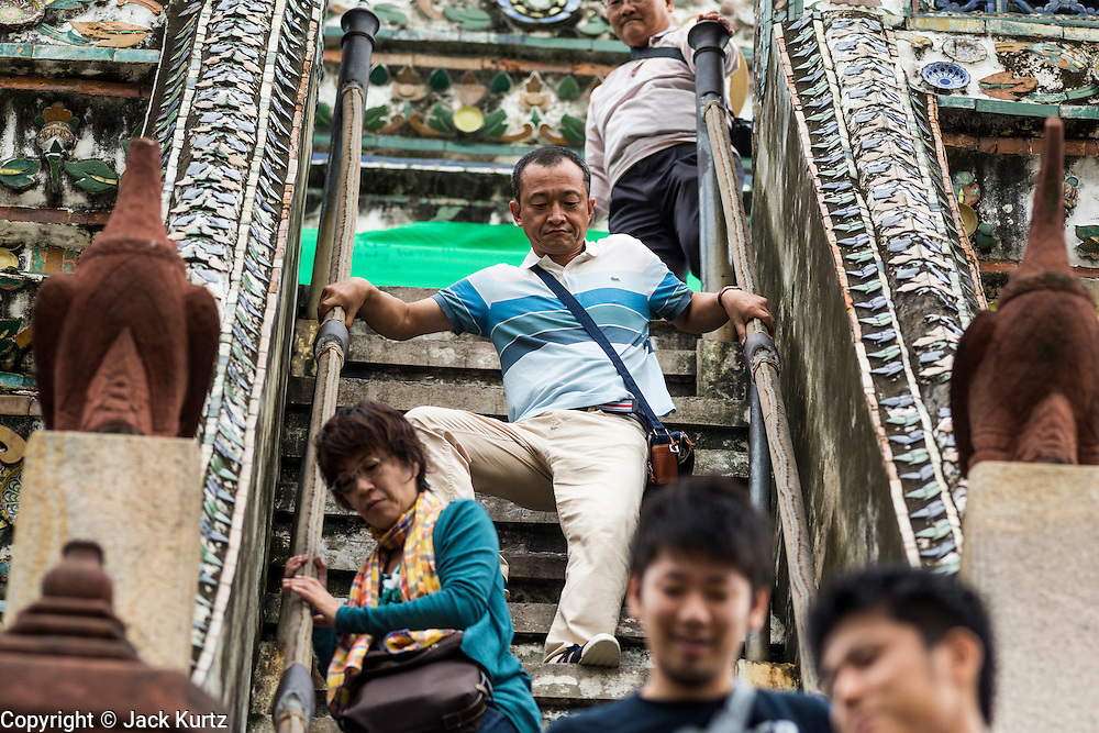 """23 SEPTEMBER 2013 - BANGKOK, THAILAND: Tourists climb down from the top of the central prang at Wat Arun in Bangkok on the last day that tourists will be allowed to climb the chedi. The full name of the temple is Wat Arunratchawararam Ratchaworamahavihara. The outstanding feature of Wat Arun is its central prang (Khmer-style tower). The world-famous stupa, known locally as Phra Prang Wat Arun, will be closed for three years to undergo repairs and renovation along with other structures in the temple compound. This will be the biggest repair and renovation work on the stupa in the last 14 years. In the past, even while large-scale work was being done, the stupa used to remain open to tourists. It may be named """"Temple of the Dawn"""" because the first light of morning reflects off the surface of the temple with a pearly iridescence. The height is reported by different sources as between 66,80 meters and 86 meters. The corners are marked by 4 smaller satellite prangs. The temple was built in the days of Thailand's ancient capital of Ayutthaya and originally known as Wat Makok (The Olive Temple). King Rama IV gave the temple the present name Wat Arunratchawararam. Wat Arun officially ordained its first westerner, an American, in 2005. The central prang symbolizes Mount Meru of the Indian cosmology. The temple's distinctive silhouette is the logo of the Tourism Authority of Thailand.         PHOTO BY JACK KURTZ"""