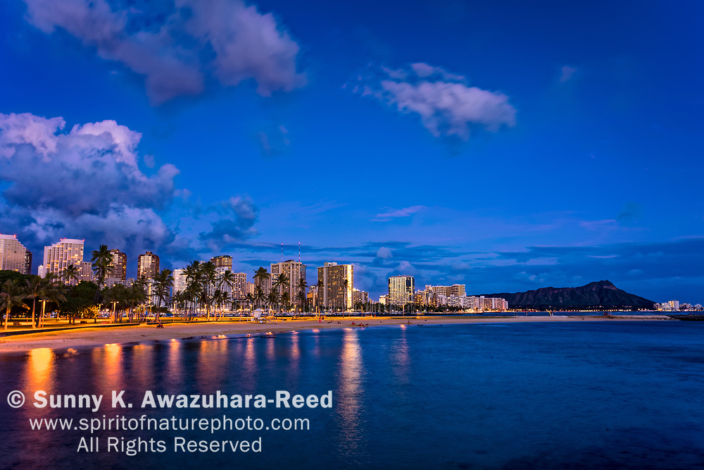 Magic Island Beach and Waikiki Skyline at dusk. Diamond Head is in the background. Honolulu, Oahu, Hawaii