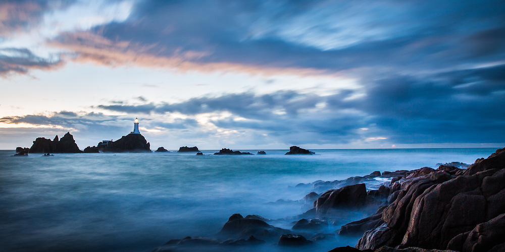 Misty blue sea and sky at Corbiere Lighthouse, a popular tourist attraction in Jersey, Channel Islands at dusk