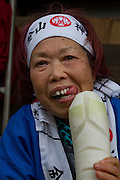An older Japanese woman plays with a large Daikon or White radish carved into the shape of a penis during the Kanamara Matsuri, (Festival of the Steel Phallus). Kawasaki Daishi, Kanagawa, Japan. Sunday April 3rd 2016. The famous Kawasaki Penis Festival started in 1977 as a small festival to celebrate an old legend about the defeat of a penis eating demon. Today the festival is a huge draw for Japanese and foreign tourists and raises money for HIV and AIDS research.