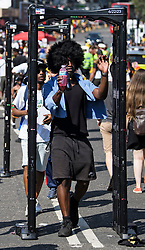 © Licensed to London News Pictures. 26/08/2019. London, UK. Carnival goers pass through a knife arch, used by police to detect knives, at day two of the Notting Hill carnival. The two day event is the second largest street festival in the world after the Rio Carnival in Brazil, attracting over 1 million people to the streets of West London. Photo credit: Ben Cawthra/LNP
