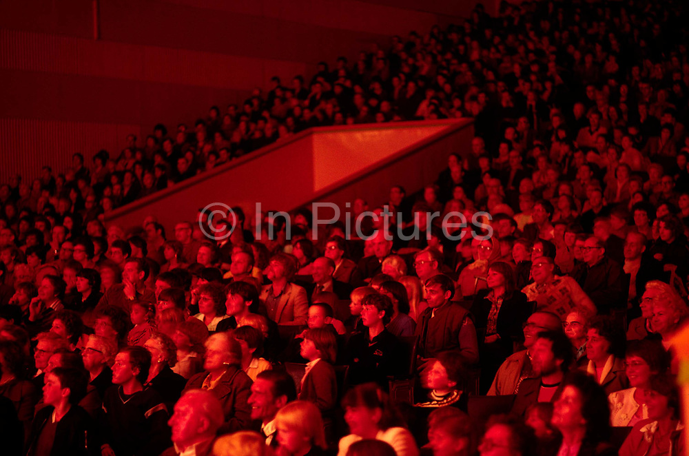A large crowd, bathed in red light, watch one of the regular evening entertainments in the Gaiety Theatre at Butlins holiday camp at Skegness. Butlins Skegness is a holiday camp located in Ingoldmells near Skegness in Lincolnshire. Sir William Butlin conceived of its creation based on his experiences at a Canadian summer camp in his youth and by observation of the actions of other holiday accommodation providers, both in seaside resort lodging houses and in earlier smaller holiday campsThe camp began opened in 1936, when it quickly proved to be a success with a need for expansion. The camp included dining and recreation facilities, such as dance halls and sports fields. Over the past 75 years the camp has seen continuous use and development, in the mid-1980s and again in the late 1990s being subject to substantial investment and redevelopment. In the late 1990s the site was re-branded as a holiday resort, and remains open today as one of three remaining Butlins resorts.