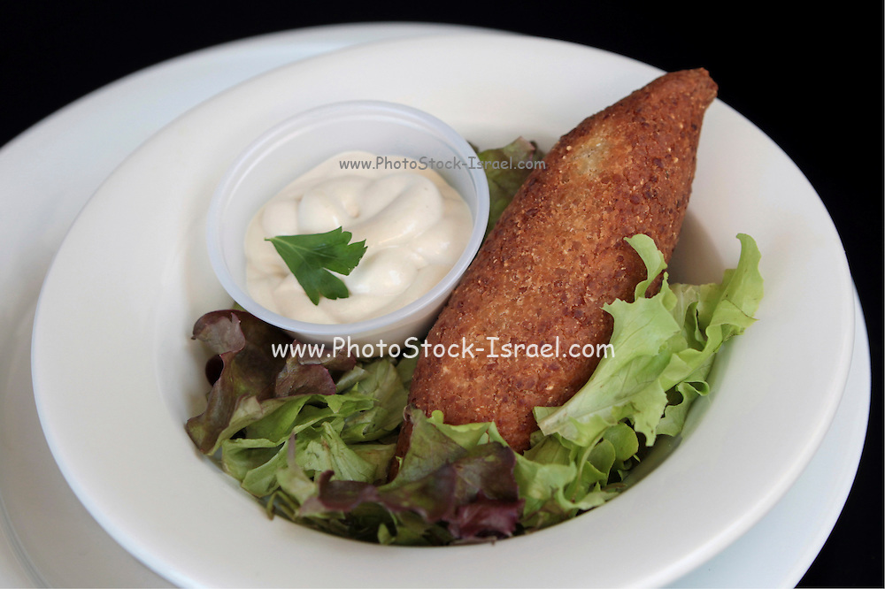 A serving of Kibbeh (also kubbeh) with Tehina and salad. Kibbeh is meat and spices wrapped in bulgur and deep fried