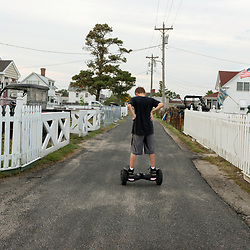August 4, 2017 - Tangier Island, VA - Jaxson Thomas takes out his new hoverboard on the street near his home in Tangier Island.  Fewer and fewer of the islands youth are becoming watermen, as many young people move off the island, uncertain about their future and liveliihood with the island's diminsishing land mass.<br /> <br /> Photo by Susana Raab/Institute