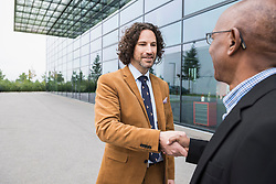Businessmen two shaking hands meeting multiracial