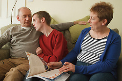Young man with autism on sofa with his parents. Cleared for Mental Health issues.