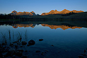 The Sawtooth Range is reflected in Little Redfish Lake at dawn in Stanley Basin, Idaho