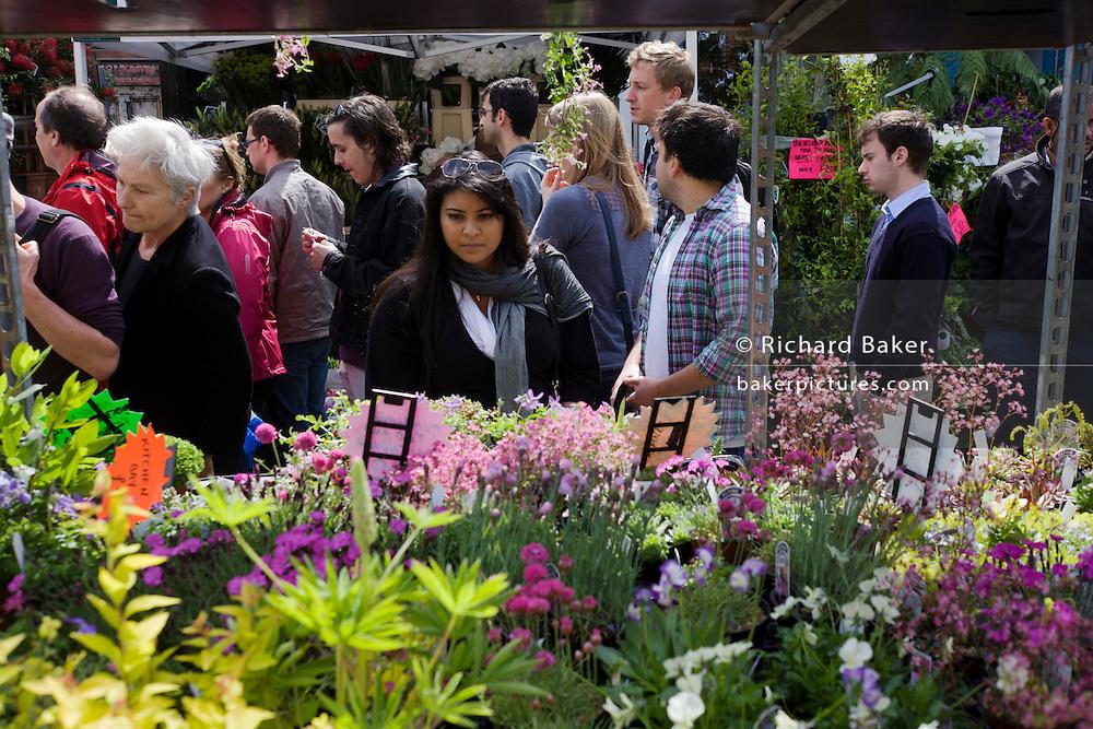 Crowds walk past fresh plants in Columbia Street flower market, in north London.