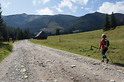 A lady walker makes her way along the stony road in Dolina Chocholowska, a hiking route in the Polish Tatra mountains, on 17th September 2019, near Zakopane, Malopolska, Poland.
