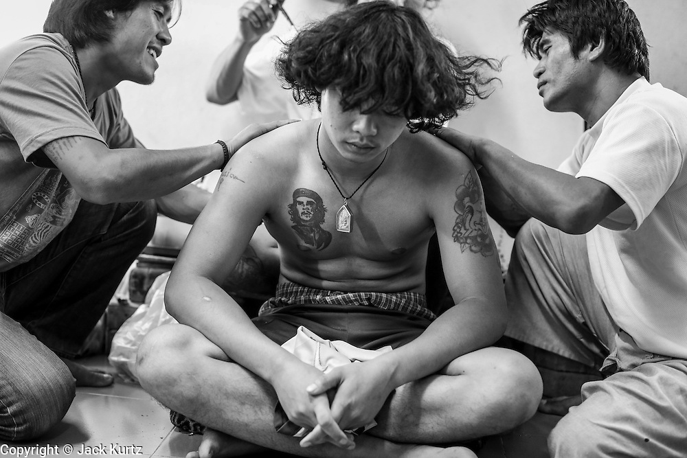 """15 MARCH 2014 - NAKHON CHAI SI, NAKHON PATHOM, THAILAND: A teenager gets a sak yant tattoo at Wat Bang Phra. Wat Bang Phra is the best known """"Sak Yant"""" tattoo temple in Thailand. It's located in Nakhon Pathom province, about 40 miles from Bangkok. The tattoos are given with hollow stainless steel needles and are thought to possess magical powers of protection. The tattoos, which are given by Buddhist monks, are popular with soldiers, policeman and gangsters, people who generally live in harm's way. The tattoo must be activated to remain powerful and the annual Wai Khru Ceremony (tattoo festival) at the temple draws thousands of devotees who come to the temple to activate or renew the tattoos. People go into trance like states and then assume the personality of their tattoo, so people with tiger tattoos assume the personality of a tiger, people with monkey tattoos take on the personality of a monkey and so on. In recent years the tattoo festival has become popular with tourists who make the trip to Nakorn Pathom province to see a side of """"exotic"""" Thailand.   PHOTO BY JACK KURTZ"""