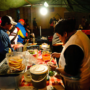 Dinner at a street food vendor as part of a night market set up for the holiday of Our Lady of Guadalupe Day in Antigua, Guatemala.
