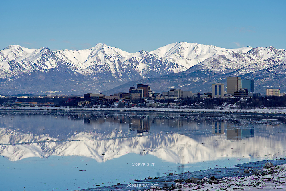 View of downtown Anchorage from Earthquake Park, with Knik Arm in the foreground and the Chugach Range in the background.