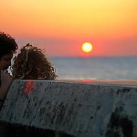 Central America, Cuba, Havana. Couple share a sunset moment on the Malecon in Havana.