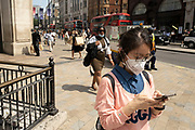 Young woman looks intently at his smartphone as the national coronavirus lockdown three eases towards the planned Freedom Day in just over two weeks, and people, many of whom are still wearing face masks while out on the street, come to Oxford Street shopping district on 22nd July 2021 in London, United Kingdom. Now that the roadmap for coming out of the national lockdown and easing of restrictions is set, dome medical professionals are suggesting thatsome safety measures are kept in place because of the increase in the Delta variant.