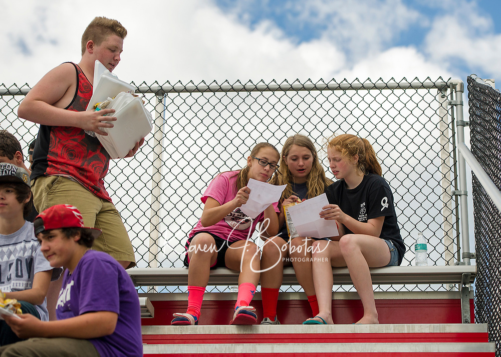 Kayleigh Thoroughgood, Katie Theberge and Caitlin Beattie check their first semester schedules following the bbq lunch provided during LHS freshmen orientation on Thursday morning.  (Karen Bobotas/for the Laconia Daily Sun)