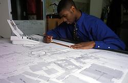 Trainee draughtsman at drawing board, UK