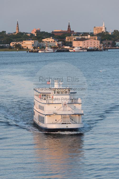 Sunset tour boat Spirit of Carolina crosses the Ashley River with the city skyline behind at sunset in Charleston, South Carolina.