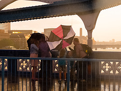© Licensed to London News Pictures. 06/07/2014. London, UK. A family struggle with umbrellas during a sudden rain shower on Tower Bridge this evening just before sunset. Photo credit : Vickie Flores/LNP
